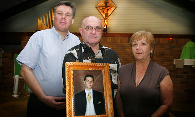 Fr Tim Harris with Lee and Christine Rush, holding a picture of Scott Rush.