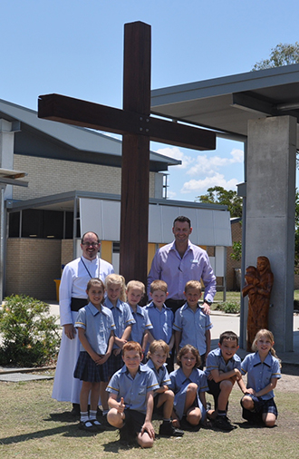Depicting history: Burpengary parish priest Oblate Father Paul Smithers (left) and assistant principal for religious education at St Eugene College, Burpengary, Nick Fogarty with students around the new Cross