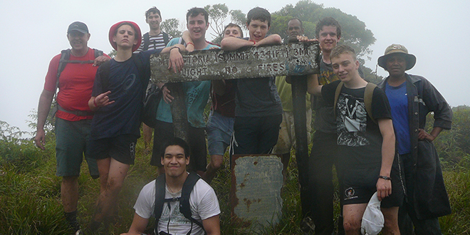 Walking in faith: Vocations director Fr Morgan Batt, left, with young men on the VOCadventure Program at the summit of Mt Victoria, Fiji