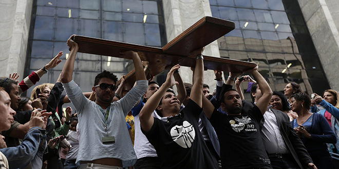 World event: Young people carry the World Youth Day cross to city hall in Rio de Janeiro on July 10 as Brazilians make final preparations for World Youth Day and the visit by Pope Francis. Young people from around the globe with join the pontiff for the celebration in Rio from July 23-28. Photo: CNS photo/Ricardo Moraes, Reuters