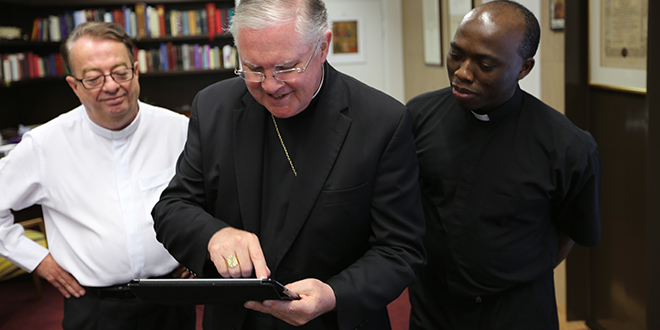 Archbishop Mark Coleridge of Brisbane checks out the new app with vicar general Monsignor Peter Meneely and St Stephen's Cathedral associate pastor Fr Anthony Ekpo.