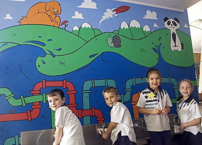 Prep students Jackson Lawry, Brodie Saunders, Chelsea Panozzo and Gisele Vitiello check out their amazing mural while getting a drink of water.