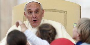 Pope Francis reacts to children as he addresses pilgrims in St Peter's Square.