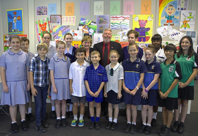 Bruce and Denise Morcombe with students in front of just some of the hundreds of safety hero entries for the new student protection primary school poster.