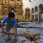 Rebuilding: An altar server lifts up a broken crucifix as he and others clear debris from the sanctuary of the partially destroyed Metropolitan Cathedral in Palo, the Phillippines, on November 15 in the aftermath of Typhoon Haiyan.