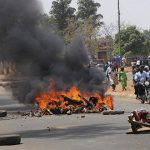 Debris blocking a road burns after a bombing at St. Finbar Catholic Church in the Rayfield suburb of the Nigerian city of Jos