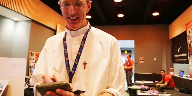 Gospels downloading: Missionaries of God's Love Father Dave Callahan downloads the new MGL app onto a nearby Android smartphone at the Australian Catholic Youth Festival.