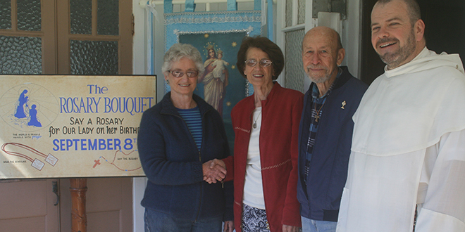 Former co-ordinator Regina O'Shaunessey hands the Universary Rosary Bouquet into the hands of Gail and Kevin Shorthouse outside their new office at Marian Valley, with Pauline Father Columba Macbeth-Green.