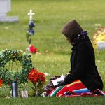 Paulina Montiel prays after placing flowers and statues of saints on her son's grave at Queen of Heaven Catholic Cemetery in Hillside, Illinois, on November 1.