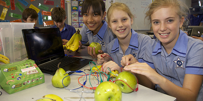 New skills: Students Melissa Suess, Kate Soeters and Laro McIntyre get to grips with computer game Fruit Ninjas using real fruit as controllers.