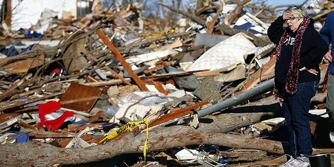 A woman reacts as she looks at what is left of her home after it was destroyed during a tornado in Washington, Illinois.