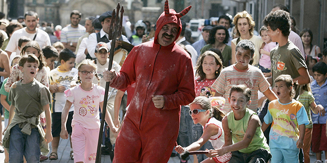 """Children chase a man dressed as a devil during a local festival called """"Fiesta del Demonio"""" (Festival of Demons) in Pontevedra, Spain."""