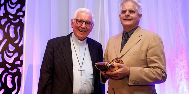 Fr Tom Elich (right) receiving his award from Wollongong Bishop Peter Ingham.