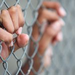 prisoner's hands through fence