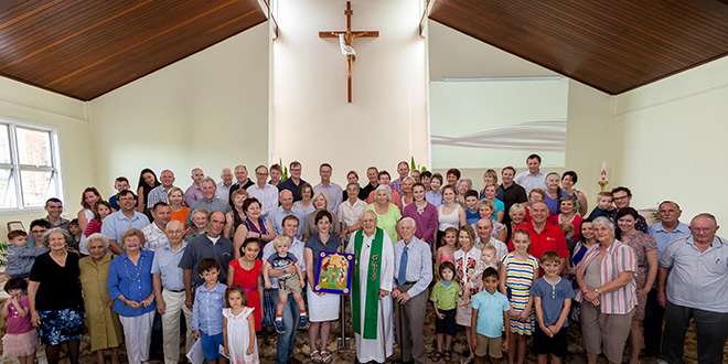 Grateful community: The community of St Carthage's Church, Gordon Park, gathers with Andrew Burke and Zara Weedon after the couple presented an icon to the parish to honour their son Angus; and (below) Andrew and Zara with the icon, which now hangs to one side of the altar. Photos: Alan Edgecomb