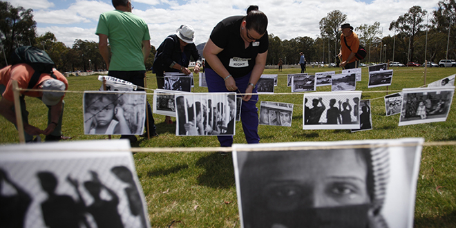 Answers needed: A woman sets up pictures of refugees during a protest to support asylum seekers, in front of Parliament House in Canberra. Catholic Religious Australia has criticised the Government on issues relating to asylum seekers. Photo: AAP/Daniel Munoz