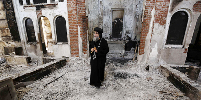 """Hope building: A Coptic Orthodox bishop surveys the damaged church in Minya, Egypt. Egypt's military and interim government have condemned all the attacks on Christian properties, calling them the """"work of terrorists,"""" and blaming them on the Muslim Brotherhood and other groups supportive of ousted leader Mohammed Morsi. Photo: CNS/Louafi Larbi, Reuters"""