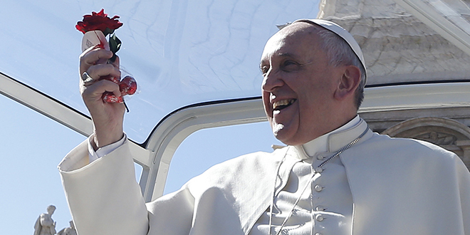 Building on love:  Pope Francis holds a rose and chocolates thrown by a person in the crowd as he arrives for an audience for engaged couples in St Peter's on Valentine's Day. Photo: CNS/Paul Haring