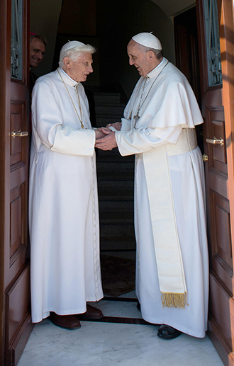 Working together: Pope Emeritus Benedict XVI greets Pope Francis in Vatican City. Photo: CNS/Paul Haring