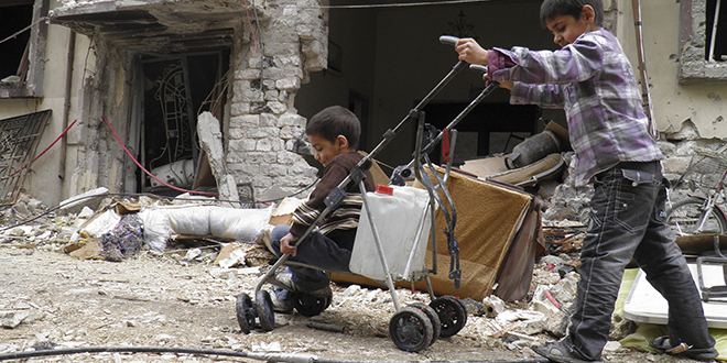 Danger zone: A boy pushes a stroller holding water and another child past destroyed buildings in the besieged area of Homs, Syria. Syrians fleeing to neighbouring Jordan from Homs said some people there were starving to death for lack of food; and (below) Bishop Antoine Audo of Aleppo. Photo: CNS/Thaer Al Khalidiya, Reuters; Other: ACN