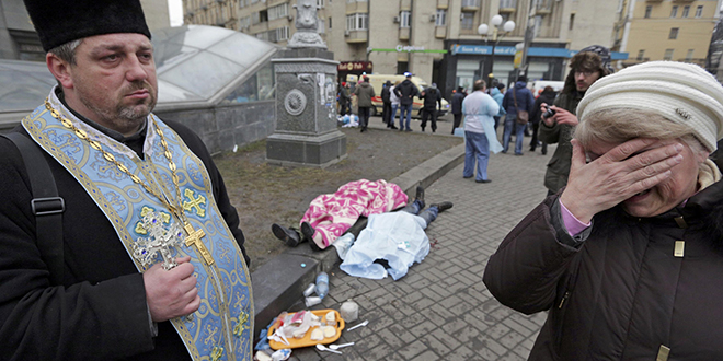 Death in Kiev: An Orthodox priest holds a cross as a woman weeps next to dead bodies following violence in Independence Square in Kiev, Ukraine, on February 20. Photo: CNS/Konstantin Chernichkin, Reuters