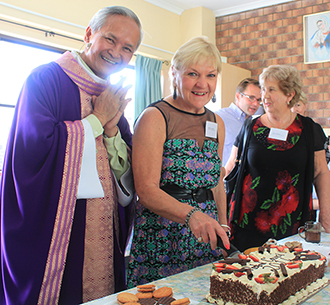 Fr Khoai and council chairwoman Ronnie Wilson at the cutting of a cake to mark the installation of the new council.