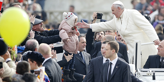 Migrant pope: Pope Francis blesses a child as he arrives to lead his general audience in St Peter's Square. Photo: CNS/Tony Gentile, Reuters