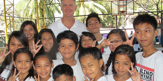 Inspirational attitude: Paul O'Callaghan with some of the local children on his recent visit to the Philippines as head of Caritas Australia.