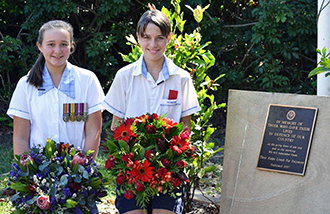Honoured: Students Hudson Diviak and Charlie Barber lay wreaths at a memorial to fallen ANZACs at St Kevin's, Benowa.