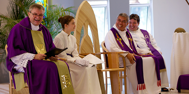 Missionary zeal: Fr Jan Bialasiewicz, left, reacting with joy during his installation to Southport parish, and seated beside altar server Toni Hawkins, Fr Teri Nueva and Fr Domenico Muscari. Photo: Janene Meyer
