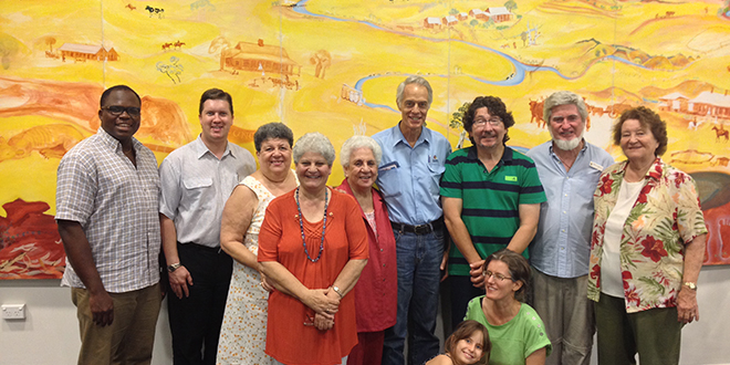 New centre: Deacon Chukwudi Chinaka and Fr Jason Middleton stand with members of the St Joseph's parish in front of a mural by one of Gayndah's local artists, on display at the Gayndah Arts and Cultural Centre.