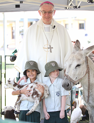Lasting legacy: Bishop Michael Putney with young students at a Townsville Diocese Mission Mass.