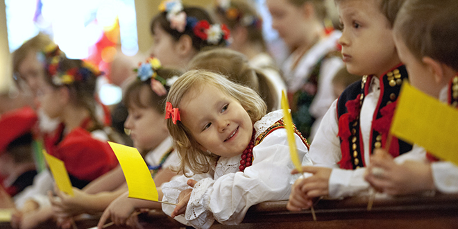 Saints remembered: Maja Gan, 3, centre, wearing traditional Polish clothing, smiles at her friends during a Mass of thanksgiving for the canonisations of Saints John Paul II and John XXIII on April 27 at St Stanislaus Kostka Church in Rochester, New York. Pope Francis canonised the two former popes earlier that day in Vatican City. Photo: CNS/Mike Crupi, Catholic Courier
