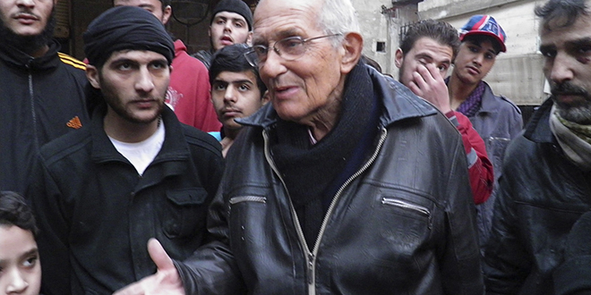 Murdered: Jesuit Father Frans van der Lugt chats with civilians in early January, urging them to be patient, in the besieged area of Homs, Syria. The Jesuits said on April 7 that the Dutch priest, who had worked in Syria since 1966, was beaten by armed men and killed with two bullets to the head. Photo: CNS/Thaer Al Khalidiya, Reuters