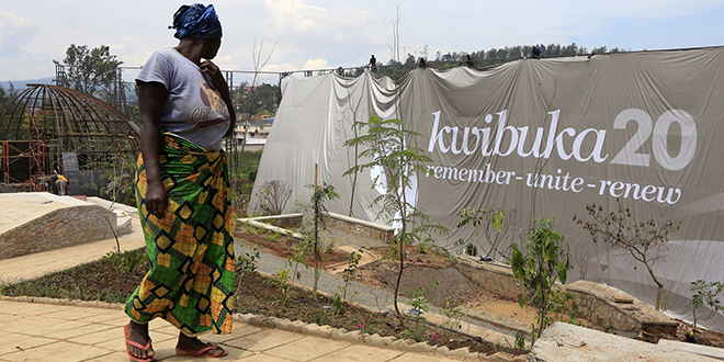 "Tragic events: A laborer walks past a banner on April 2 that reads ""Remembering 20 years"" at the Kigali Genocide Memorial grounds as the country commemorate the 20th anniversary of the 1994 Rwandan genocide. Photo: CNS/Noor Khami, Reuters"