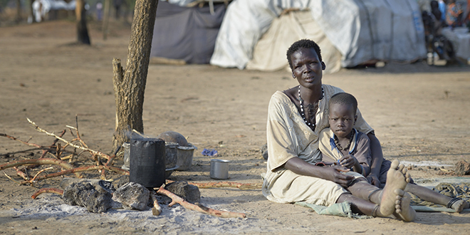 Call for peace: Anyuak Ring Deng and her five-year-old daughter Arual sit under a tree in an internally displaced persons camp in Manangui, South Sudan. Families started arriving at the camp soon after fighting broke out in December. Photo: CNS/Paul Jeffrey