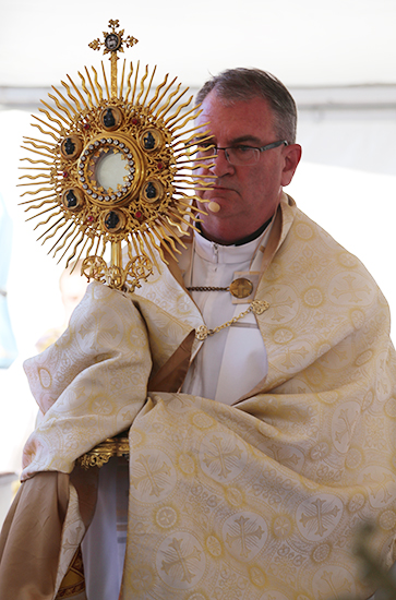 Cathedral dean Fr David Pascoe with the Blessed Sacrament during Benediction at the Corpus Christi procession.