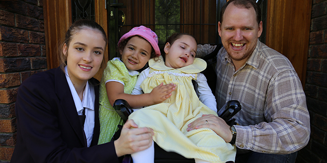 Miracle girl: Gabby Caldwell (centre) with Lourdes Hill College's L'Arche and Disability Outreach service group captain Laura Ricco, younger sister Sophia Caldwell and father Kevin Caldwell. Photo: Emilie Ng