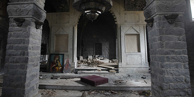 Damaged: Paintings of Mary and Christ are seen in the damaged Um al-Zenar church in Homs, Syria. Photo: CNS/Khaled al-Hariri, Reuters
