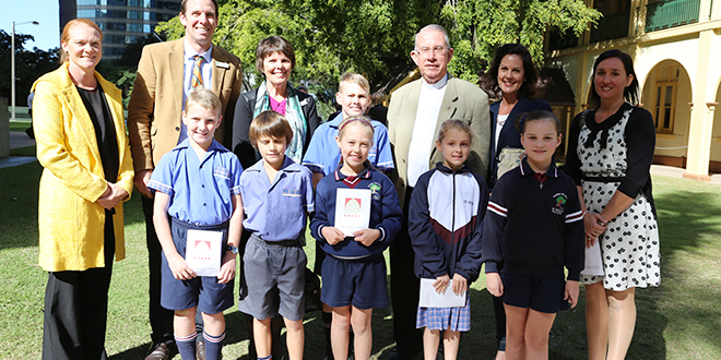 Golden times: Fr Leo Burke (fifth from right) with Candace Holden, Shane Thompson, Thomas Johnstone, Owen Loft, Anne McKenny, Jacob Dunne, Alice Connor, Brianna Saunders, Frances Connor, Faye Holden, and Riane Loft from St Rita's Catholic primary school.