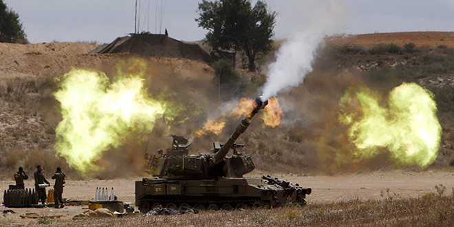 Escalating: An Israeli mobile artillery unit fires toward the Gaza Strip on July 18. Pope Francis telephoned Israeli President Shimon Peres and Palestinian President Mahmoud Abbas July 18, urging all sides to end hostilities and build peace. Photo: CNS/Nir Elias, Reuters