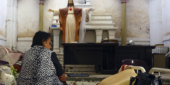 Seeking refuge: An Iraqi Christian woman fleeing the violence in the Iraqi city of Mosul sits inside the Sacred Heart of Jesus Chaldean Church in Telkaif, Iraq, on July 20. Photo: CNS/Reuters