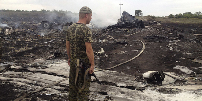 An armed pro-Russian separatist stands at the site of a Malaysia Airlines Boeing 777 plane crash on July 17 in Grabovo, Ukraine. It is believed all 295 people aboard died in the crash. Photo: CNS/Maxim Zmeyev, Reuters