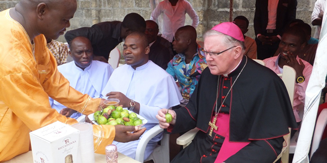 Memorable journey: Brisbane Archbishop Mark Coleridge warily chooses a kola nut – eaten with a paste of peanuts and chilli and also a fruit called a tree-egg – during his visit to the Diocese of Umuahia in Nigeria.