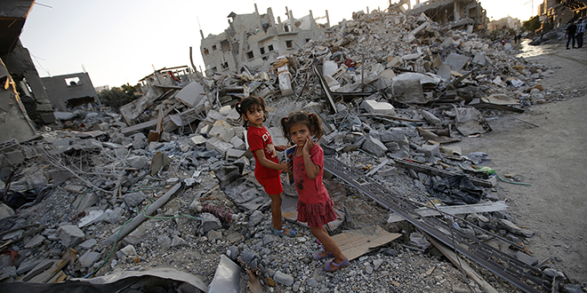 "Damage control: Two Palestinian sisters walk among the rubble of their destroyed home in the Gaza Strip on August 12. A senior Catholic aid official said humanitarians are ""trying to pick of the pieces"" of Gaza's badly destroyed infrastructure, hoping that the truce between Israel and the militant Hamas will hold. Photo: CNS"