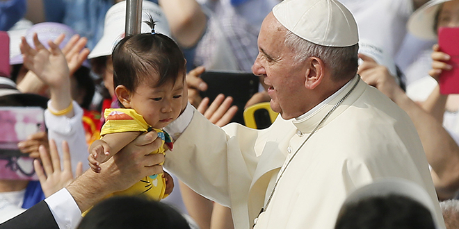 First visit: Pope Francis greets a child as he arrives to celebrate the beatification Mass of Paul Yun Ji-chung and 123 martyred companions in Seoul, South Korea. Photo: CNS/Paul Haring