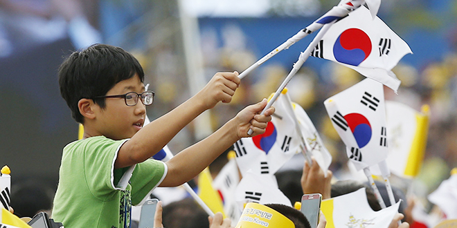 A boy waves South Korea's flag as he cheers before Pope Francis' arrival at a rehabilitation centre for people with disabilities in Kkottongnae, South Korea. Photos: CNS /Paul Haring