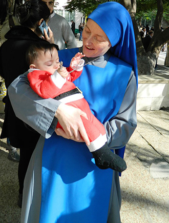 Devoted helper: Sister Maria de Nazaret during the annual pre-Christmas visit of the Latin Patriarch to Gaza. She later volunteered to go to Aleppo in Syria. Photos:  Aid to the Church in Need
