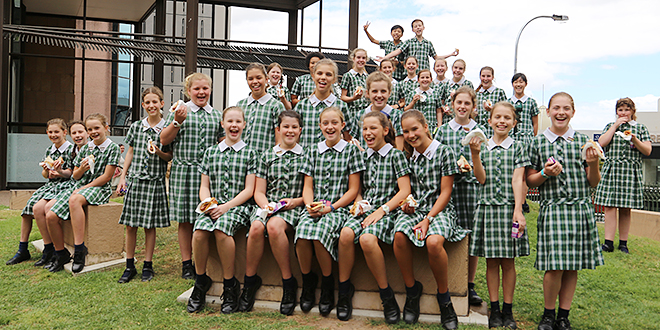 Good helpings: Year 6 and 7 students from Holy Family School, Indooroopilly enjoy a sausage sizzle lunch donated by Bendigo Bank, a Catholic Mission sponsor. Photo: Emilie Ng