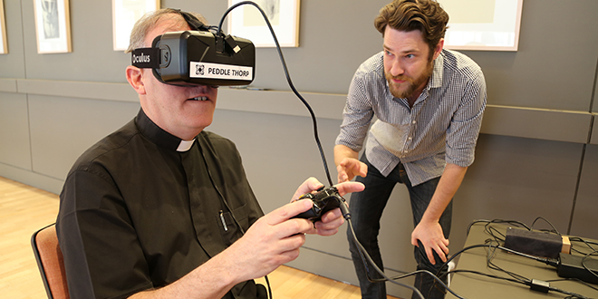 Virtual vision: Peddle Thorp design systems specialist Tom de Plater talks to Burleigh Heads parish priest Fr Ken Howell as he uses the virtual reality headset and gaming console to take a virtual tour through the new Burleigh Waters church. Photo: Emilie Ng